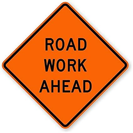 Image of orange construction sign stating &#34Road Work Ahead&#34