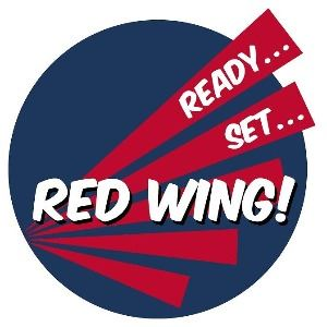 Logo of Ready Set Red Wing! featuring a dark blue circle and stylized red wing with the words Ready.