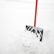 Image of a black shovel with red handle sunk into a mound of snow