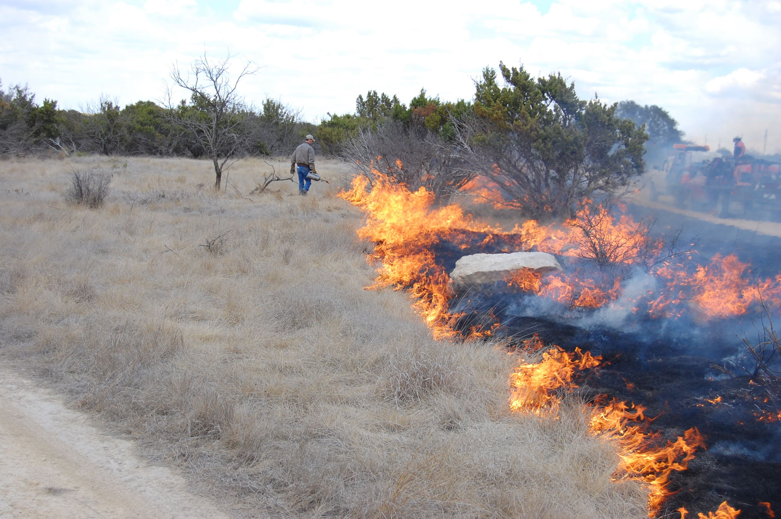 Man Operating a Controlled Grass Fire