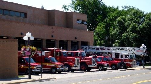 Firehouse with firetrucks and emergency service vehicles in front of it